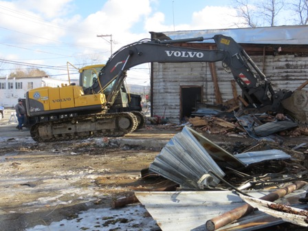 excavator tearing down building